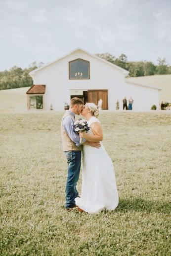 Bride and Groom in front of barn at Maypop Fields Wedding and Event Venue
