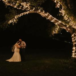 Outdoor wedding under grand oak tree at night.