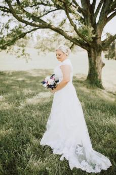 Bride under grand oak tree at Maypop Fields Wedding and Event Venue